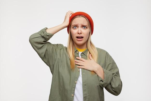 Sconcertata giovane donna bionda dai capelli lunghi dagli occhi azzurri aggrottando le sopracciglia confusamente e tenendo la mano alzata sulla testa, in posa sul blu