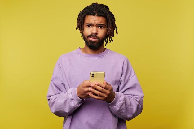 Озадаченный молодой кареглазый темнокожий брюнет держит смартфон в поднятых руках и смущенно смотрит в камеру, стоя на желтом фоне