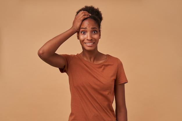 Sconcertata giovane donna riccia dalla pelle scura dagli occhi marroni alzando la mano alla testa mentre guarda confusamente, in piedi sul beige