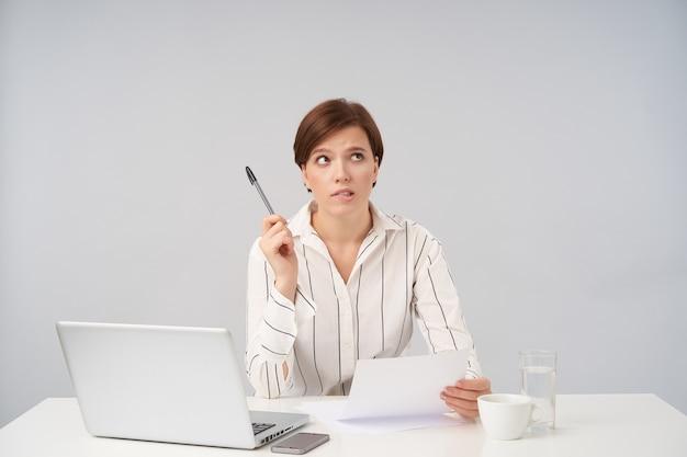 Sconcertata giovane donna d'affari dai capelli castani vestita in abiti formali tenendo carta e penna mentre posa su bianco, mordere il labbro inferiore e guardando confusamente verso l'alto