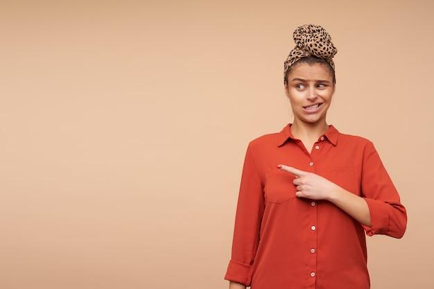 Sconcertato giovane donna dai capelli castani con trucco naturale torcendo la bocca mentre mostra confusamente da parte con il dito indice, in piedi sopra il muro beige