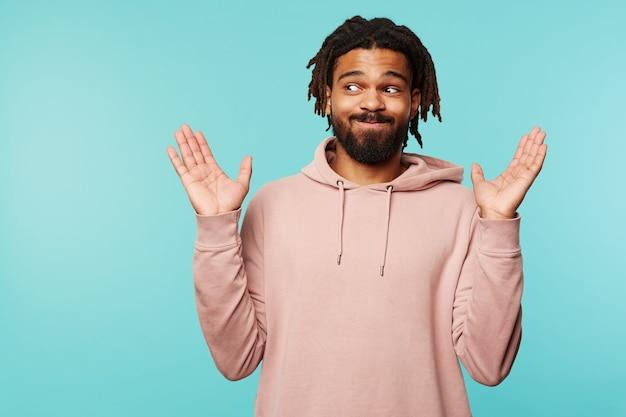 Sconcertato giovane brunetta maschio barbuto alzando confusamente i palmi e gonfiando le guance mentre guarda da parte, indossando abiti casual mentre si trova su sfondo blu