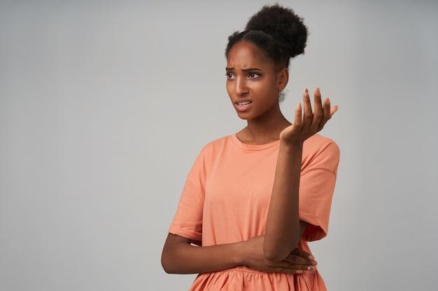 Sconcertata giovane signora bruna riccia con la pelle scura che fa una smorfia sul viso mentre solleva confusamente il palmo, in piedi sul grigio in una maglietta elegante