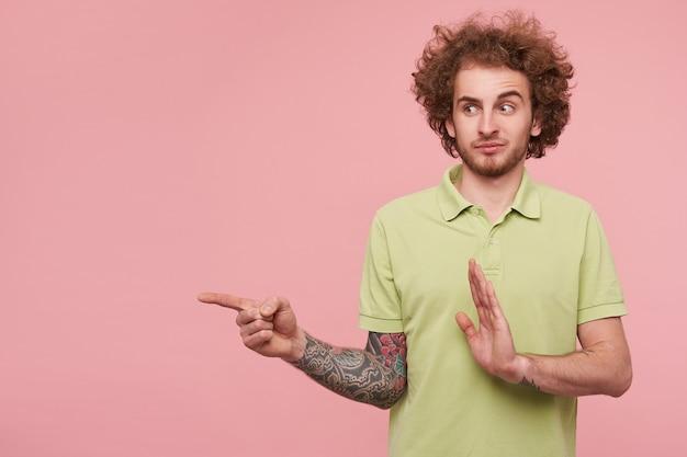 Озадаченный молодой кудрявый татуированный мужчина с брюнеткой, одетый в зеленую футболку, смущенно смотрит в сторону и показывает указательным пальцем, позирует на розовом фоне