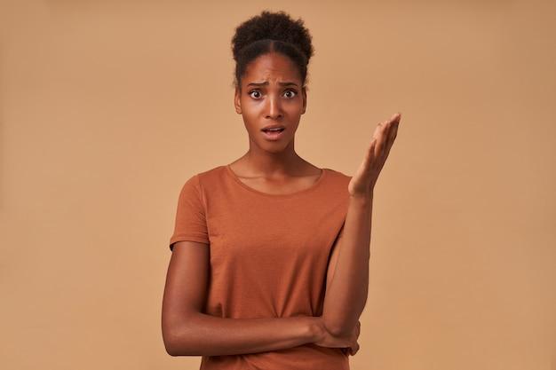 Озадаченная молодая темнокожая брюнетка, гримаснича, недоуменно поднимает руку и смущенно смотрит, позируя на бежевом.