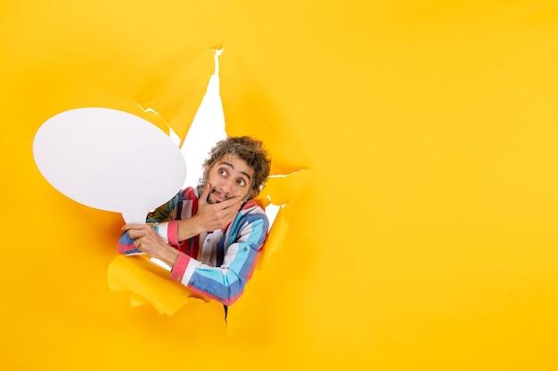 白い風船を持って、黄色い紙の引き裂かれた穴と自由な背景でカメラのポーズをとって当惑した若い男