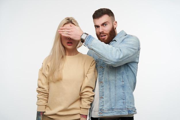 戸惑う若いハンサムな短い髪のブルネットのひげを生やした男は、白い背景の上に隔離された彼の金髪の驚いたガールフレンドの目を閉じながら手を上げます