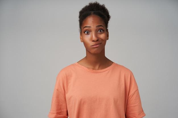 Sconcertato giovane bella donna bruna dalla pelle scura torcendo la sua bocca e faccendo smorfie mentre guarda confusamente, isolato su grigio