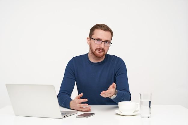 Сбитый с толку молодой симпатичный бородатый парень в очках смущенно смотрит в камеру и недоуменно поднимает ладонь, изолированный на белом фоне в синем пуловере