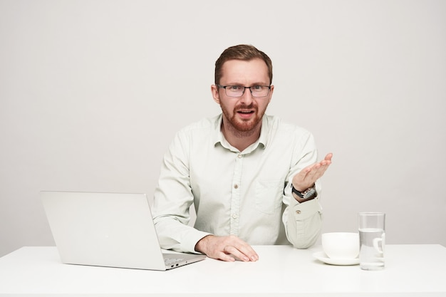 Сбитый с толку молодой симпатичный бородатый мужчина в очках недоуменно поднимает ладонь, смущенно глядя в камеру, сидя за столом на белом фоне