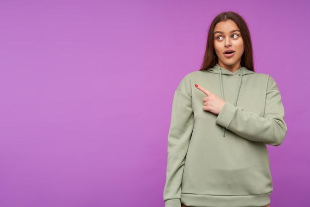 보라색 벽 위에 서서 검지 손가락으로 옆으로 보여주는 동안 손을 유지하는 자연스러운 메이크업으로 당황한 젊은 예쁜 갈색 머리 여자