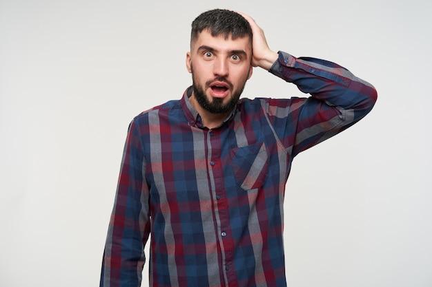 당황한 젊은 꽤 어두운 머리 수염 난 남자가 그의 머리에 손을 올리고 놀랍게도 흰 벽 위에 서있는 동안 갈색 눈을 둥글게합니다.