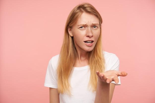 カジュアルな服装でピンクの背景の上に立っている間、彼女の目を細め、混乱して手のひらを上げる緩いセクシーな髪を持つ当惑した若いきれいな女性