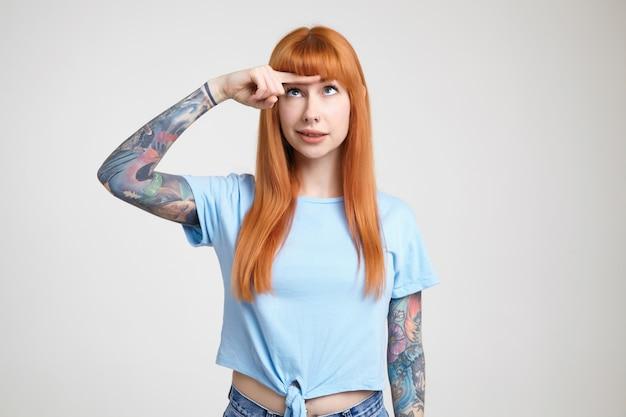 Озадаченная молодая симпатичная татуированная женщина с распущенными длинными волосами держит указательный палец на лбу и смотрит на него, стоя на белом фоне в синей футболке