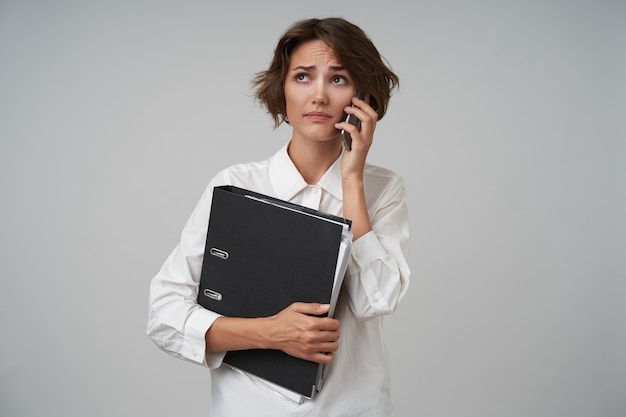 Озадаченная молодая красивая женщина с непринужденной прической, работающая секретарем и звонящая своему боссу, готовящая документы для деловой встречи, в белой рубашке