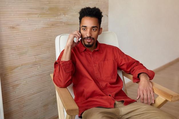 Sconcertato giovane ragazzo barbuto dai capelli corti con la pelle scura che guarda attentamente davanti a sé mentre effettua una chiamata con il suo telefono cellulare, seduto in una sedia accogliente su interni beige