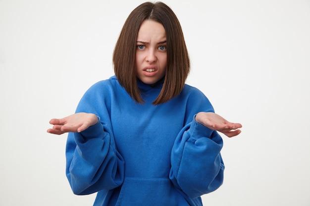 スポーティーな服装で白い壁の上に立っている間、彼女の顔を顔をゆがめ、手のひらを上げたままにする化粧のない当惑した若い短い髪のブルネットの女性