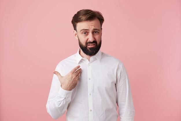 Sconcertato giovane uomo bruna non rasato con acconciatura alla moda che punta su se stesso con il broncio e la fronte rugosa, indossando abiti formali mentre si trova sul muro rosa