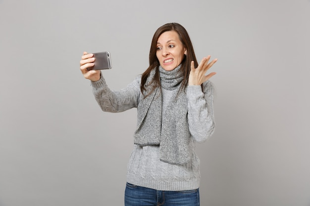 Bewildered young woman in sweater, scarf spreading hands doing selfie shot on mobile phone making video call isolated on grey background. healthy fashion lifestyle people emotions cold season concept.