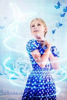 Очарованная девочка в синем платье в горошек радуется волшебству с бабочками, мечтающих попасть в фантастический сказочный мир. концепция фантазии и детских мечтаний