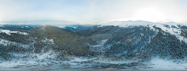 冬の曇りの日にモミの木で覆われた山や丘の魅惑的な美しいパノラマ
