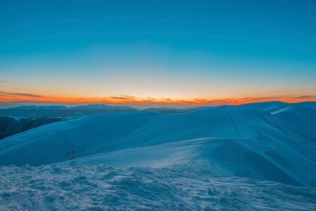 夕方遅くに雪に覆われた谷の山や丘の魅惑的な美しい景色。冬の田園地帯と冬の週末のリラクゼーションの美しさの概念。コピースペース