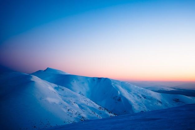 夕方遅くに雪に覆われた谷の山と丘の魅惑的な美しい景色