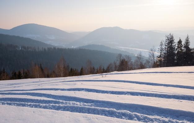 맑은 서리가 내린 날에 눈 덮인 언덕 침엽수 림과 맑은 산맥의 아름다운 전망과 함께 스키 슬로프의 매혹적인 전망. 스키장에서 휴식의 개념입니다. 텍스트 배치