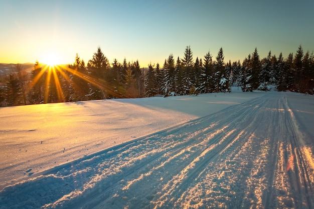 晴れた凍るような日に雪の丘の針葉樹林と日当たりの良い山脈の美しい景色を望むスキースロープの魅惑的な景色。スキーリゾートでのリラクゼーションの概念。テキストの場所