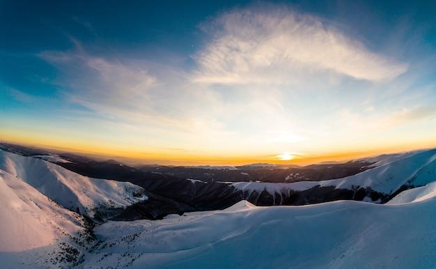 Завораживающий вид на зимние лыжные трассы в зимний солнечный вечер с ярким солнцем и голубым небом. представление о чудесах природы и красоте зимних стран. copyspace