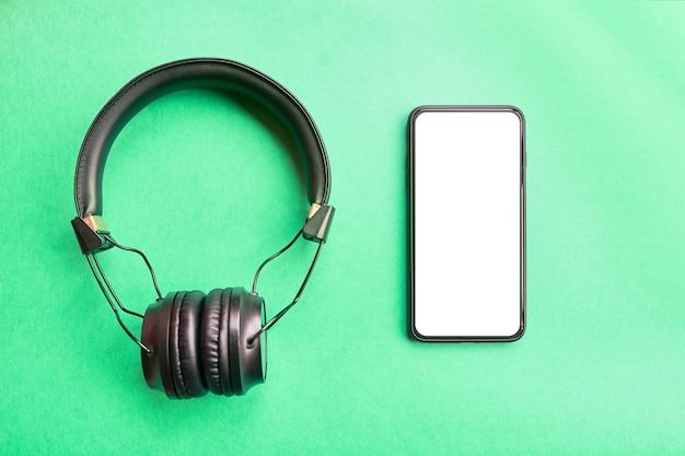 ベゼル少ないカラフルな背景にスマートフォンとワイヤレスヘッドフォンのモックアップ