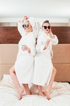 Bffの楽しみ。リラクゼーションタイム。ベッドでポーズをとるシャンパンを持つ若い女性。サングラス、バスローブ、タオルターバン。