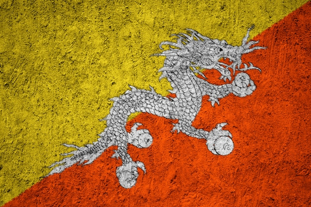 Bhutan flag on the grunge concrete wall