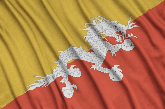 Bhutan flag is depicted on a sports cloth fabric with many folds.