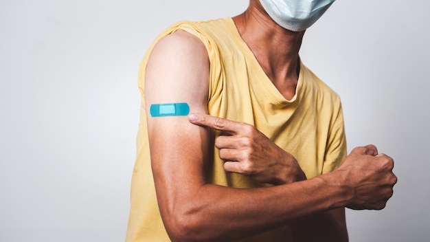 Bi-colored asian man showing vaccinated arm with adhesive patch after getting covid-19 vaccine injection.