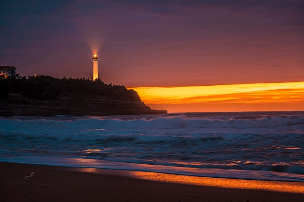Biarritz lighthouse at beach of little house of love in biarrtiz in a beautiful sunset