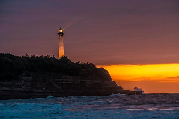 Маяк биаррица освещен красивым закатом. франция