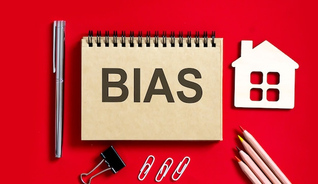 Bias text written on a notebook with pencils and office tools and model wooden house