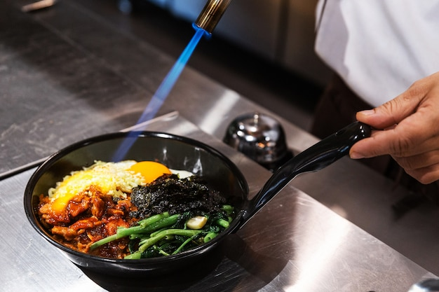 Bibimbap (korean rice mixed with kimchi pork, seaweed and stir fried vegetables topping with sesame) served on the hot pan that chef using a blow torch for melting mozzarella cheese on a fried egg.