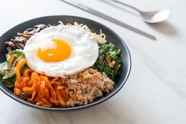 ビビンバ、ご飯と目玉焼きの韓国のスパイシーサラダ-伝統的な韓国料理のスタイル