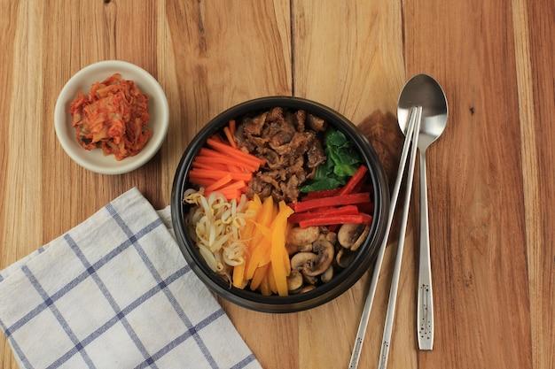 비빔밥, 쌀과 맑은 국수 계란후라이를 얹은 한국식 매운 샐러드, 한국의 전통 혼합 쌀 음식 스타일. 나무 테이블에 상위 뷰