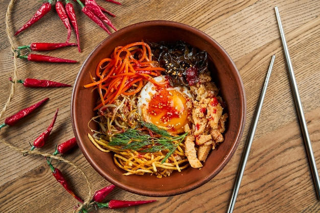 Bibimbap served as a bowl of warm white rice topped with namul, kimchi, chili pepper paste, soy sauce, fried egg and sliced meat.