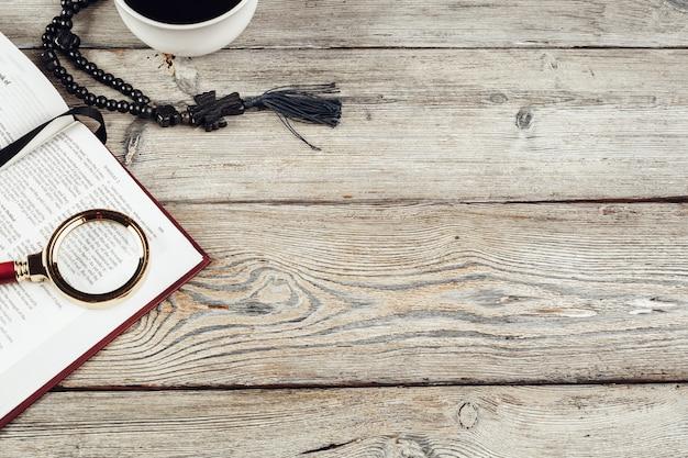 聖書と古い木製のテーブルに十字架。宗教 。