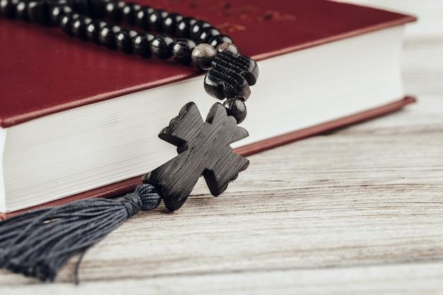 聖書と古い木製のテーブルに十字架