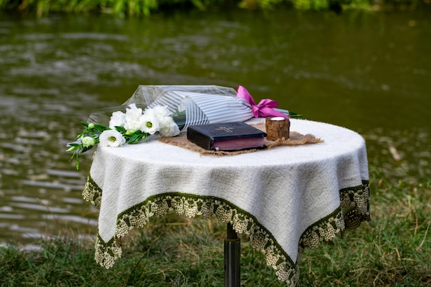 Bible, a candle and a bouquet of flowers are on the table against the river.