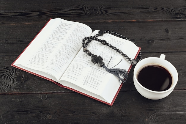 Bible and a crucifix on an old wooden table with coffee cup