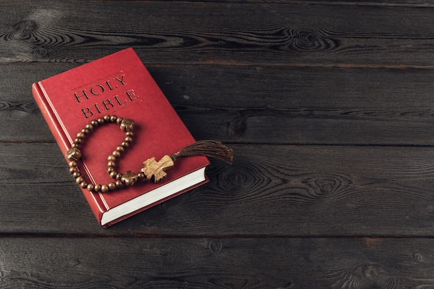 Bible and a crucifix on an old wooden table