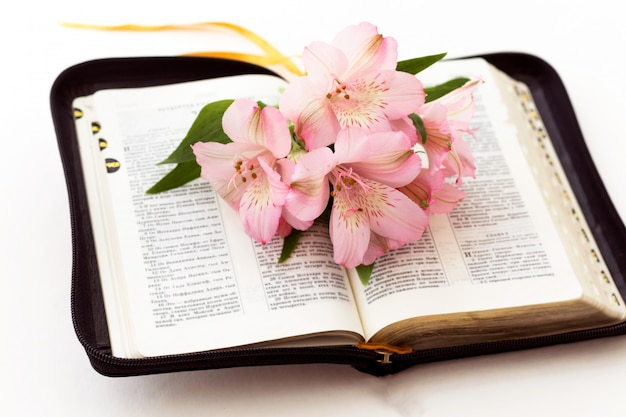 Bible and flowers on white background