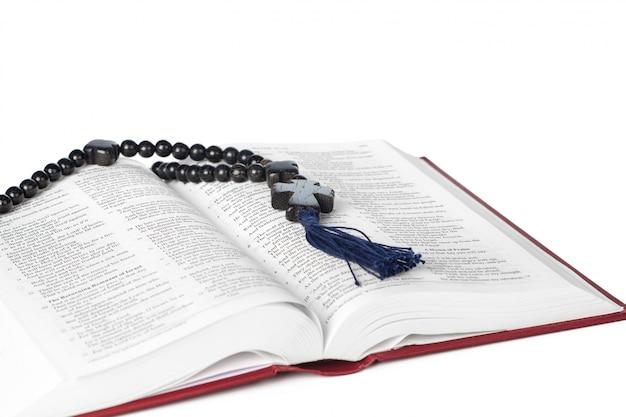 白い背景の上の聖書。神聖な本と木製の数珠。