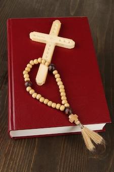 성경, 묵주 및 십자가 나무 테이블 클로즈업